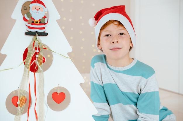 Маленький мальчик с санта-клаусом рядом украшенное дерево