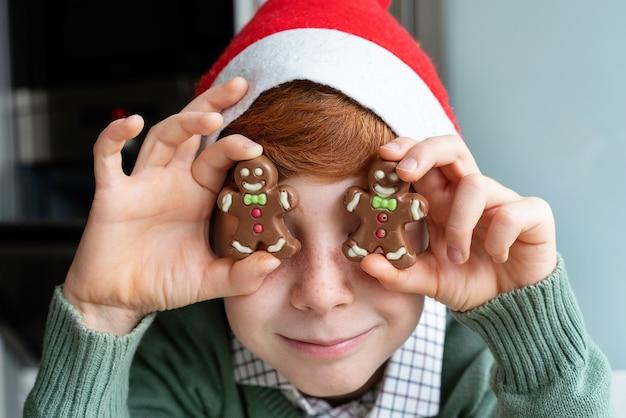 サンタの帽子とクッキーのプレートを持つ小さな男の子