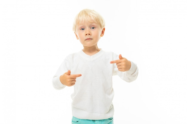 Little boy with short blonde hair, blue eyes, cute appearance, in white jacket, light blue pants, stands and is surprised