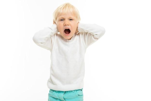 Маленький мальчик с короткими светлыми волосами, голубыми глазами кричит, изображение на белом фоне.