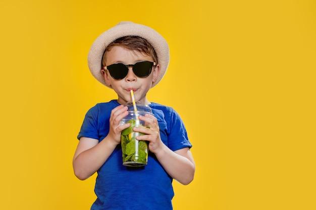 Маленький мальчик в соломенной шляпе и солнцезащитных очках пьет мохито в пластиковом стаканчике на желтом фоне