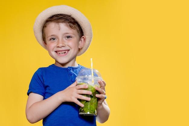 Маленький мальчик в соломенной шляпе пьет мохито в пластиковом стаканчике на желтом фоне