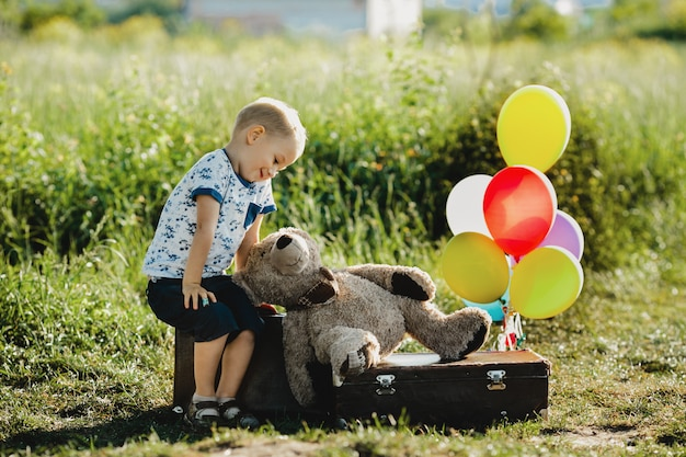 Little boy with teddy bear sits on a suitcase with colorful balloons on the field