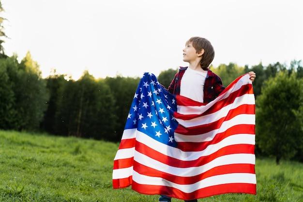 자연 속에 미국 국기가 있는 어린 소년, 애국심과 독립 미국의 개념.