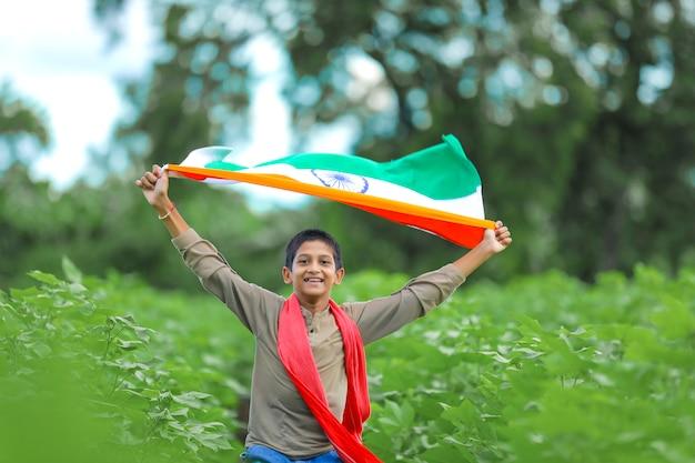 自然の中でインドの旗を持った少年