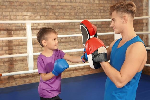 ボクシングのリングにトレーナーと小さな男の子