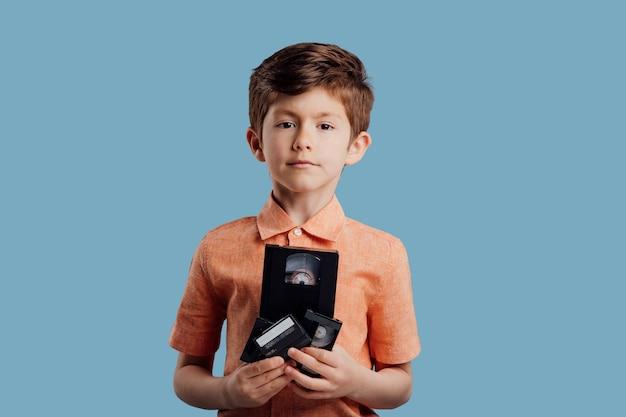 파란색 배경 오래된 가제트에 격리된 비디오 테이프를 가진 어린 소년