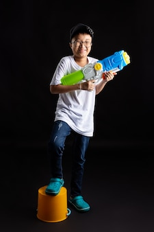 Little boy with water gun on black background