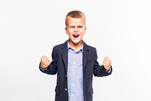 白い壁に分離された勝利のジェスチャーを持った少年