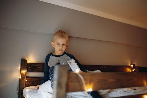 어린 소년은 크리스마스 아침에 다우블 저장 침대에서 일어났습니다.