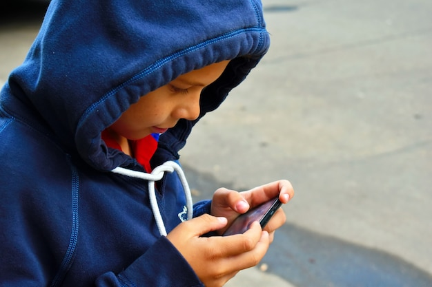 Little boy  writes sms on the mobile phone.