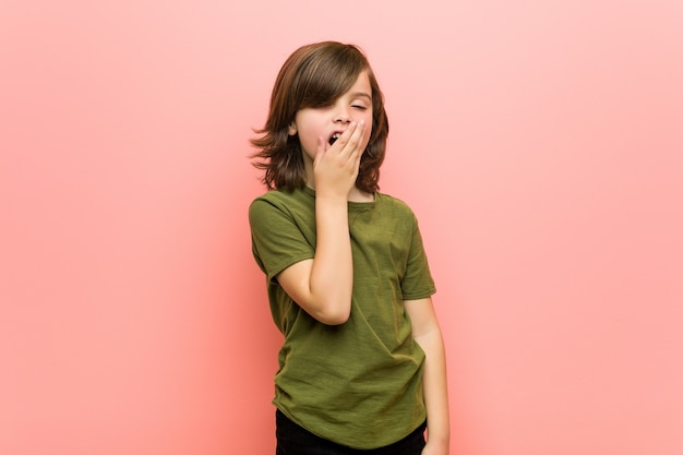 Little boy yawning showing a tired gesture covering mouth with hand