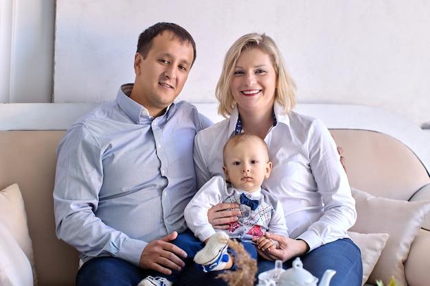 Маленький мальчик лет со счастливыми родителями сидит на диване в помещении