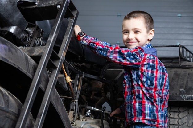 Little boy young auto mechanist cheerfully dreams that he â rides fast on a motorcycle in the garage of a service station. a child smiling and standing near on an old atv