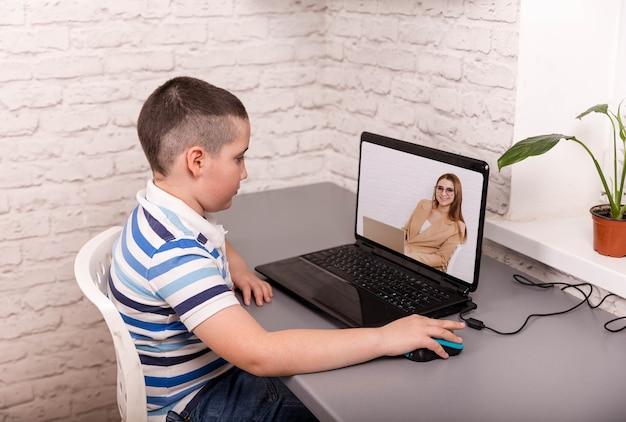 온라인 학교 수업에 참석하는 어린 소년. 꽤 세련된 남학생