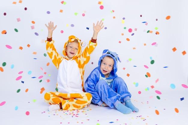 Маленькие мальчики братья в веселых ярких костюмах сидят на полу и сдувают конфетти