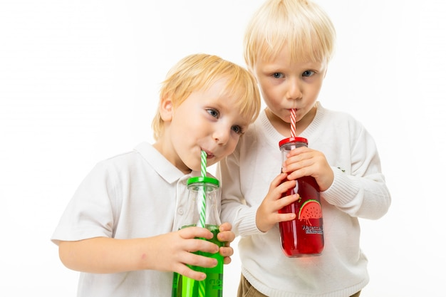 Little boys brothers with short light and red hair, blue eyes, cute appearance, in white jacket, light blue pants, stand and pose beautifully on camera and hold green and red juice in a glass bottle