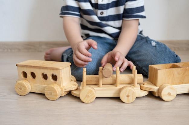 나무 기차를 노는 작은 소년 손.