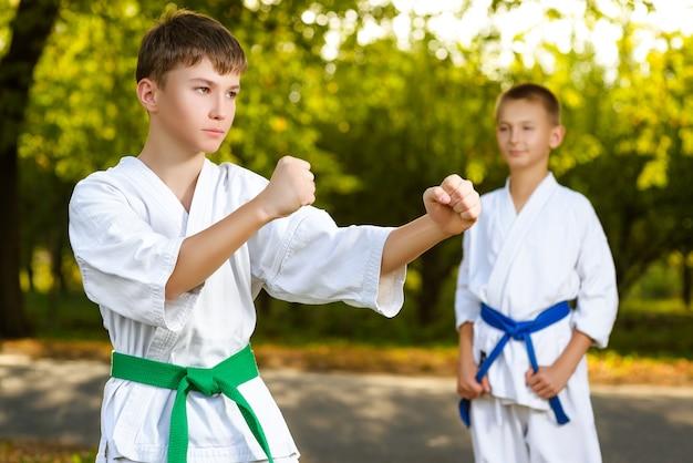 夏の屋外で空手の練習を訓練中に白い着物姿の男の子
