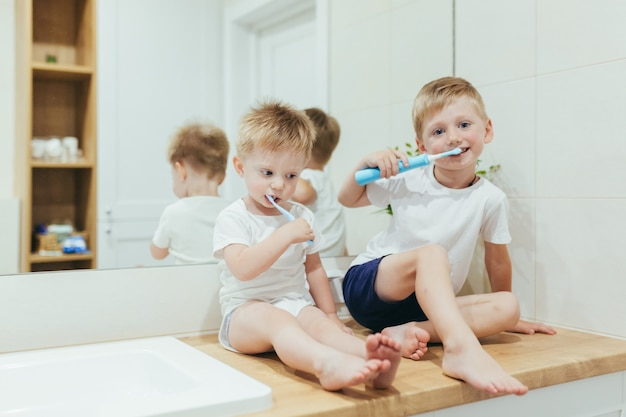 Little boys kids brushing teeth in the bathroom, two brothers
