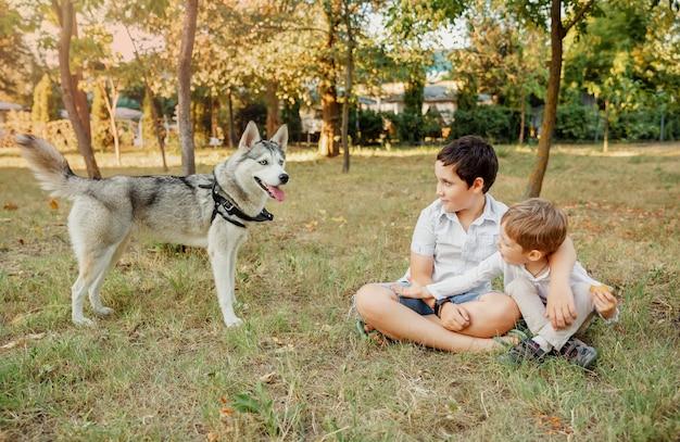 彼の愛犬を愛情を込めて抱き締める小さな男の子。アクティブで健康的なライフスタイル