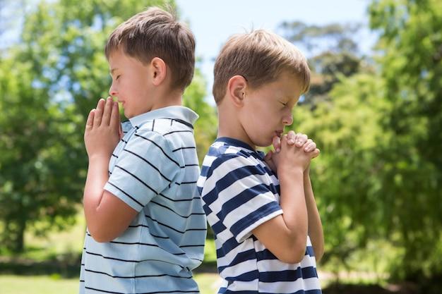 公園で祈っている少年たち