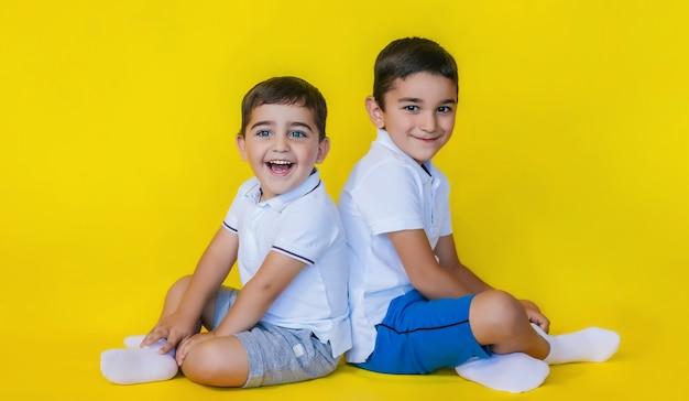 어린 소년들은 노란 벽의 바닥에 앉아 있습니다. 형제나 친구들은 미소를 지으며 즐겁게 지냅니다.