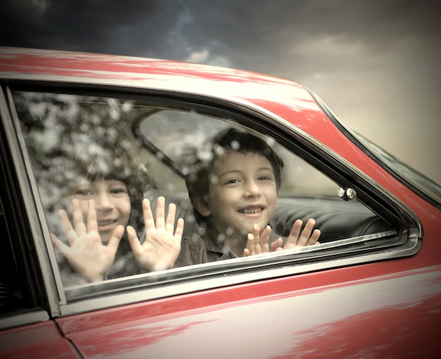 Little boys smiling from a car