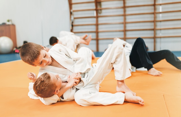 Little boys in uniform practice kid judo. young fighters on training in gym, martial art for defense