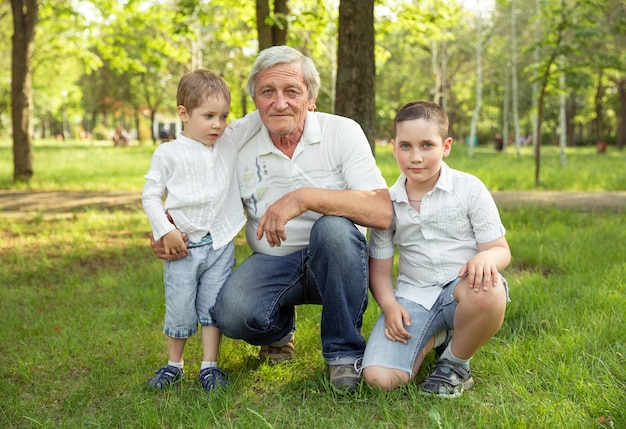 Little boys with grandfather are playing, relaxing on the grass.