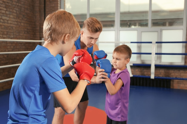 Little boys with trainer on boxing ring