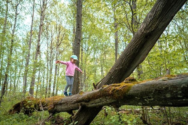 Маленькая храбрая девочка в весеннем лесу гуляет по бревну