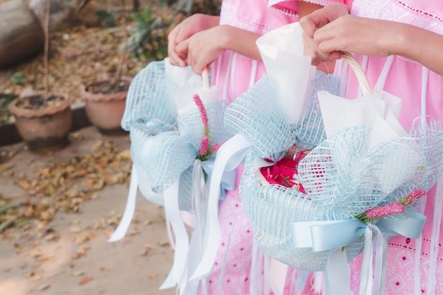 結婚式でバラの花びらのバスケットを持って保持している小さな花嫁介添人の女の子。