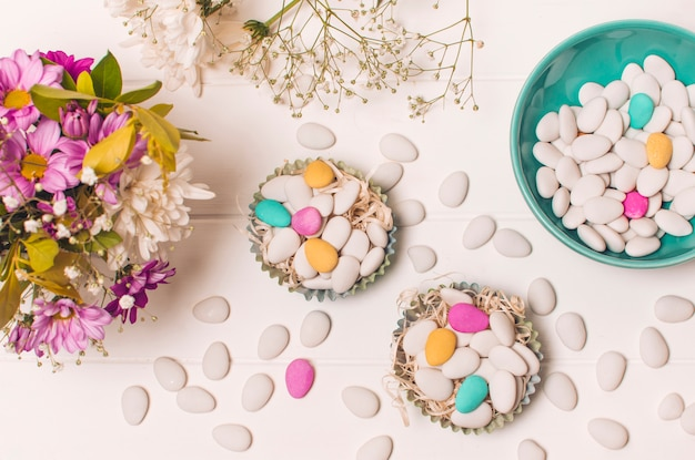 Little bright stones in baskets and bowl near flower bouquet