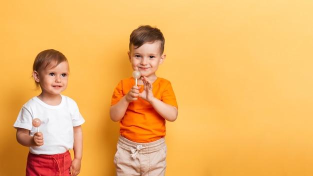 Маленькие брат и сестра едят сладкий леденец на палочке. желтый фон. концепция профилактики кариеса и диабета у детей. место для текста