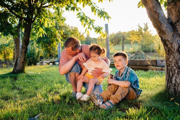 弟と妹は、日没時に美しい春の庭で父親と一緒に苗を植えています。新生活。環境を守ろう。周囲の世界と自然に対する慎重な態度。