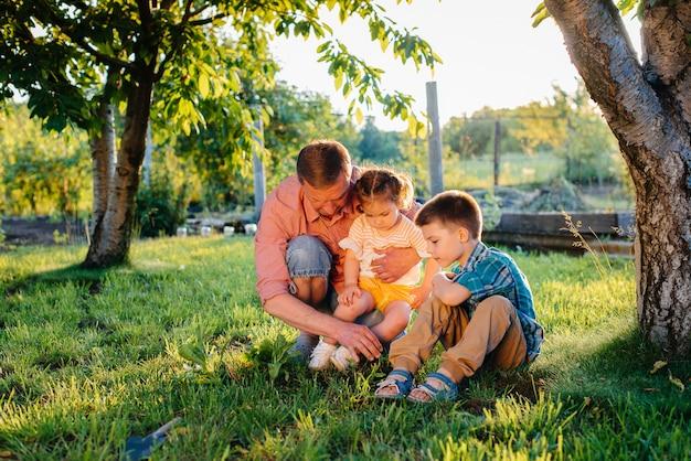 Младший брат и сестра сажают саженцы с отцом в прекрасный весенний сад на закате. новая жизнь. сохранить окружающую среду. бережное отношение к окружающему миру и природе.