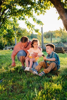 Маленькие брат и сестра сажают саженцы вместе с отцом в красивом весеннем саду на закате. новая жизнь. сохранить окружающую среду. бережное отношение к окружающему миру и природе.