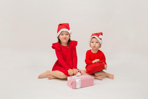 白い壁に贈り物とキャップとクリスマスの衣装を着た弟と妹