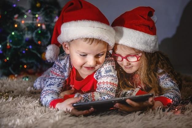 산타 모자를 쓴 남동생은 푹신한 격자 무늬 위에 누워 패드를 봅니다. 뒤에 크리스마스 트리가 있습니다