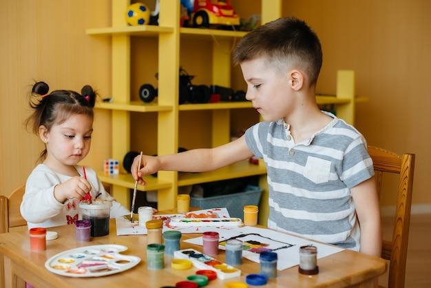 Младший брат и сестра рисуют вместе
