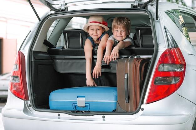 Маленький брат и сестра сидят на заднем сиденье автомобиля семейной поездки