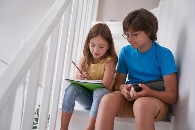デジタルタブレットを使用して自宅の階段に座ってオンラインで学習している弟と妹または