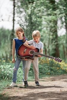 도시 공원에서 산책을 위해 기타를 든 남동생과 자매. 행복한 어린 시절의 개념