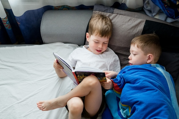 弟は長老のためにベッドで本を読みます。兄弟間の友情。読書が大好きです。人々の間でヒバリとフクロウ。ベッドの上の2人の男の子が1冊の本を読んでいます。おとぎ話
