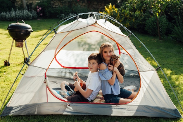 Little brother and sister enjoying picnic while sitting in tent