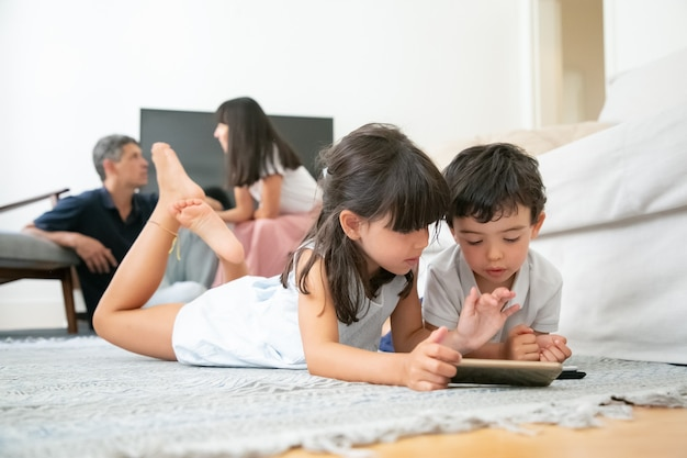 Piccolo fratello e sorella sdraiati sul pavimento in soggiorno e utilizzando gadget digitali con app di apprendimento mentre i genitori si siedono insieme