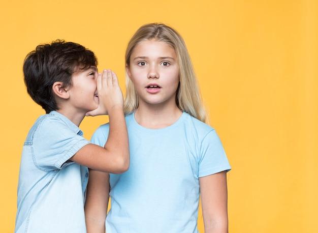 Little brother whispering secret to sister