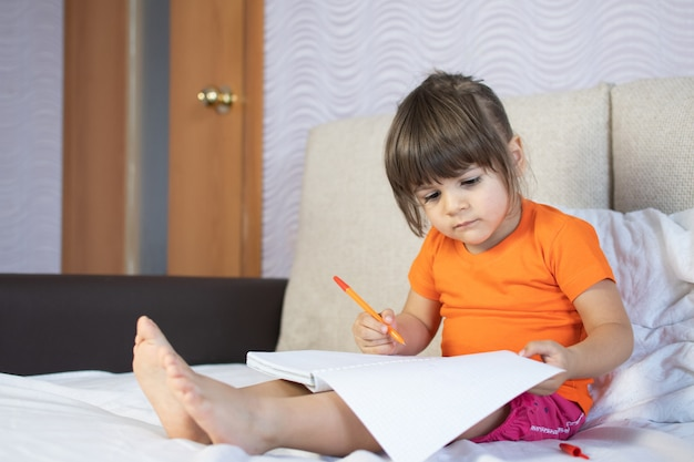 Маленькая девочка каштановых волос с карими глазами. 3 года. живопись пером в блокноте. сидя дома на диване. наслаждайтесь рисованием.