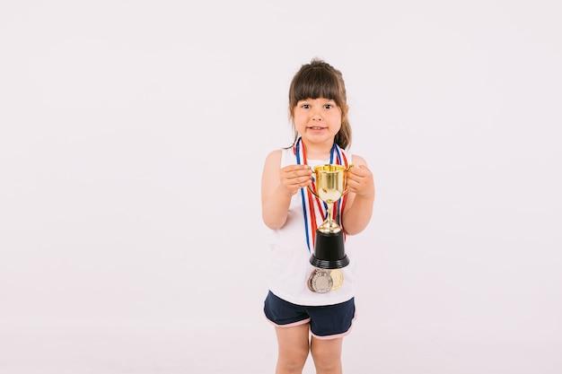 두 손으로 트로피를 들고 스포츠 챔피언 메달을 가진 작은 갈색 머리 소녀. 스포츠와 승리 개념